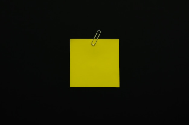 Yellow blank note paper with paper clip on dark background. minimalist flat lay black concept.