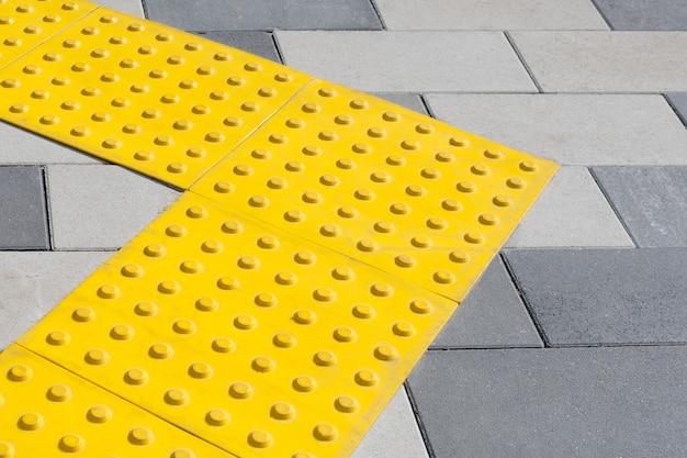 盲目のハンディキャップのための触覚舗装の黄色いブロック。点字ブロック、視覚障害者用触覚タイル、天地ブロック
