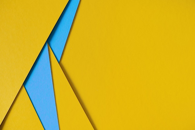 Yellow and blue geometric composition paperboard background with copyspace