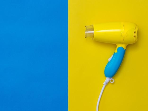 파란색 옆에 노란색 배경에 노란색-파란색 헤어 드라이어. 화려한 배경에 머리카락을 건조시키는 장치.