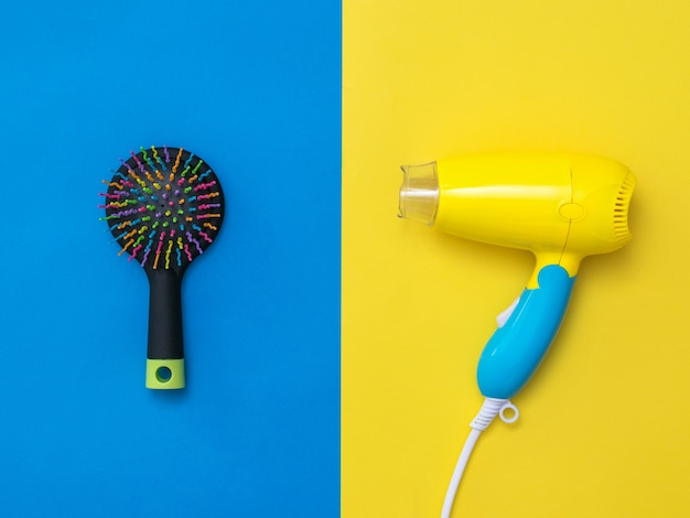 Yellow-blue hair dryer and a small comb on a yellow and blue surface. devices for drying hair on a colorful surface.