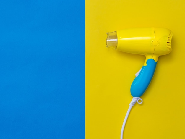 Yellow-blue hair dryer on a yellow background next to the blue. devices for drying hair on a colorful background.