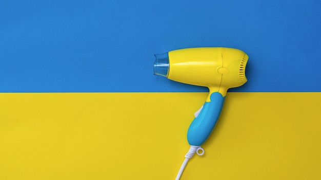Yellow-blue hair dryer on a yellow-blue surface. devices for drying hair on a colorful surface.