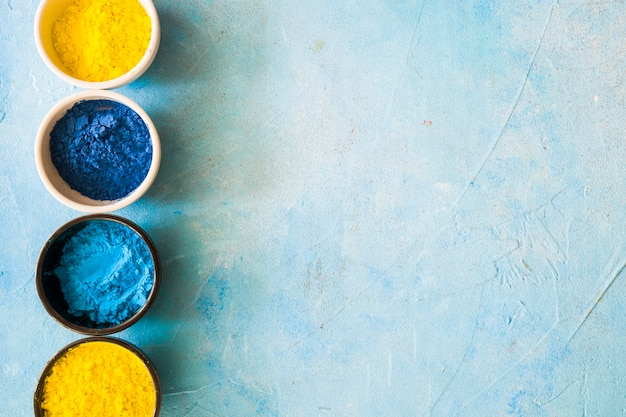 Yellow and blue holi color powder in bowls on concrete painted background