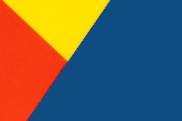 黄色青赤色の紙の背景。幾何学的図形、形状。抽象的な幾何学的な平らな構成。