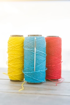 Yellow; blue and red yarn spool on wooden desk