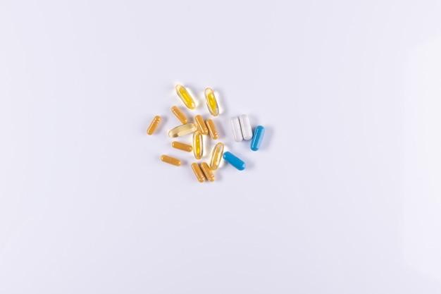 Желто-синие белые таблетки и капсулы, лежащие на белом фоне крупным планом омега