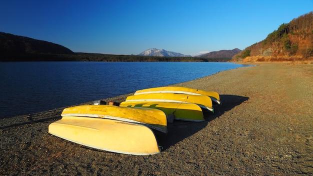 Желтые лодки, сделанные из старого дерева для рыбаков, отправляются на рыбалку к красивому озеру и ясному голубому небу в районе фудзи токио, япония. Premium Фотографии