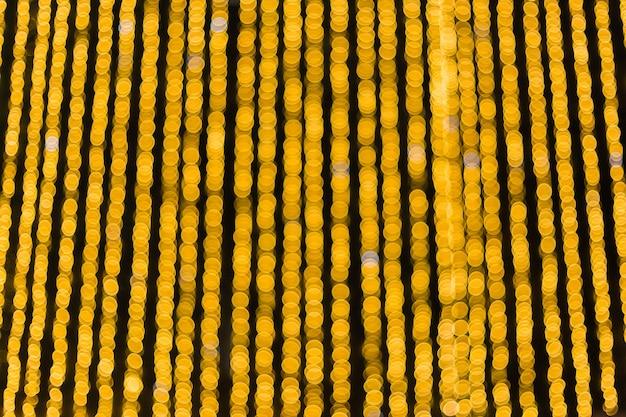 Желтый фон шары боке. золотой праздник светящийся фон. расфокусированным фон с мигающими звездами.