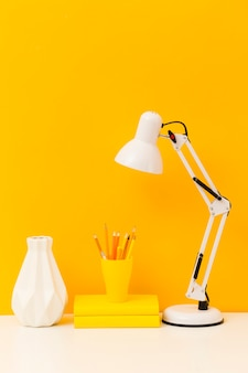 Yellow books and desk lamp front view
