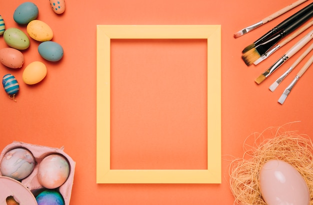 Yellow border frame surrounded with easter eggs; nest and paint brushes on an orange background