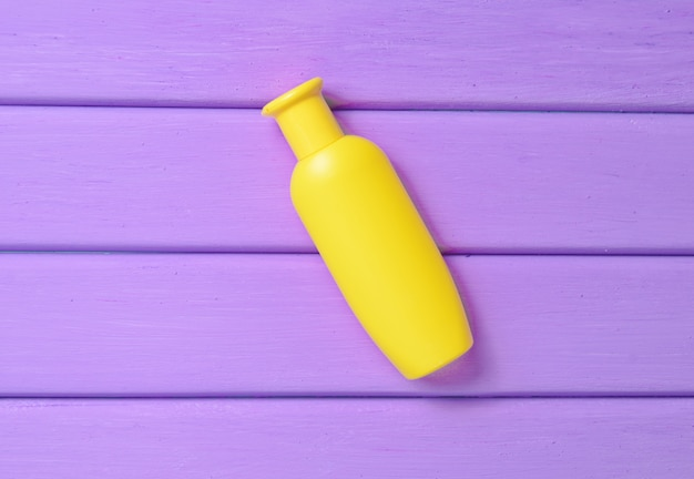 A yellow bottle of shampoo on a purple wooden table.