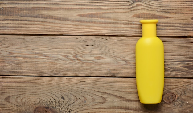 A yellow bottle of shower gel on a wooden table. shower products. top view.