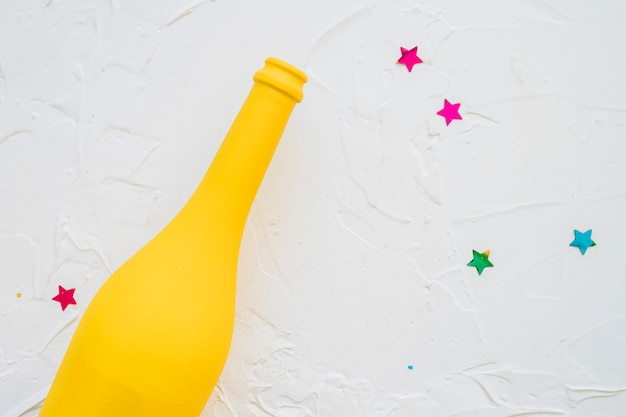 Yellow bottle with star spangles on table