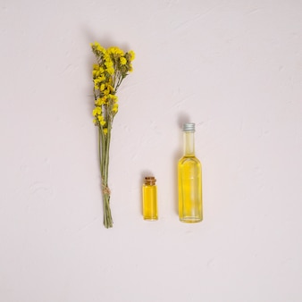 Yellow bouquet of limonium flowers with essential oil bottles on white concrete backdrop