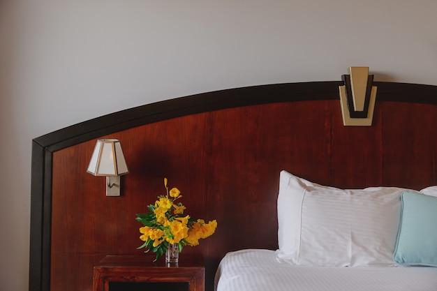 ホテル内部のベッドサイドテーブルに黄色い花束