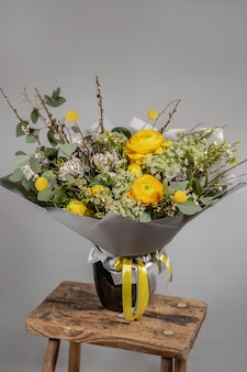 Yellow bouquet of yellow and orange flowers on grey gray background