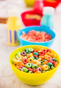 Yellow bowl of cereal with milk bottles