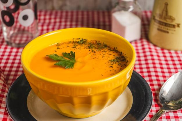 スカッシュとニンジンのスープのクリームと黄色いボウル水平フレーミングクローズアップ