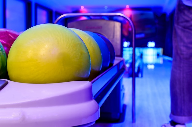 A yellow bowling balls has ready for player to throwing ball on the wooden lane