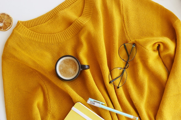 Yellow bright sweater with notepad, pen, glasses and a cup of coffee