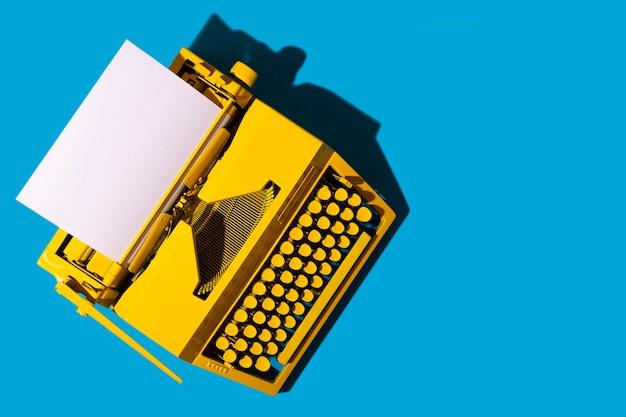 Желтая яркая пишущая машинка на синей поверхности