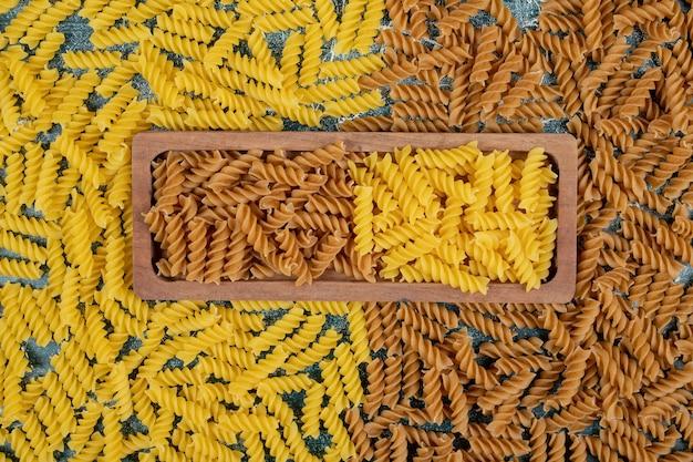 Pasta fusilli cruda gialla e marrone sul piatto di legno.
