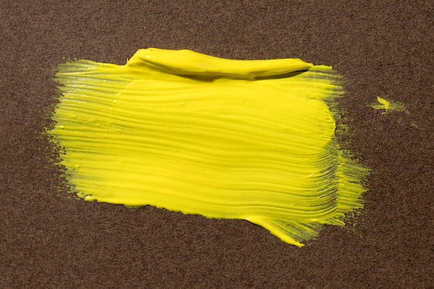 Желтый мазок кисти на коричневом фоне