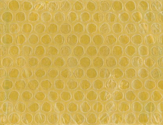 Желтая пузырчатая пленка из пластика и бумаги текстуры фона