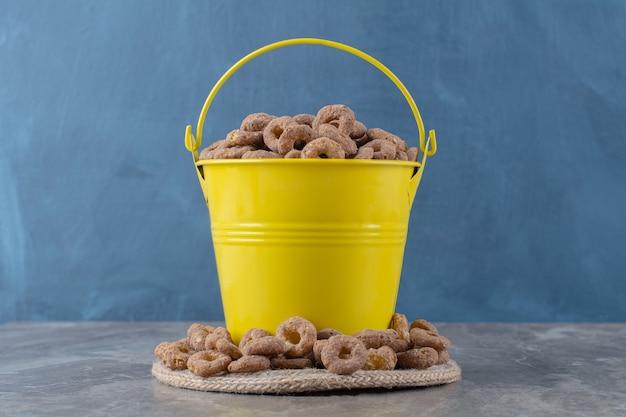 Un secchio giallo pieno di cereali gustosi sani su tela di sacco.