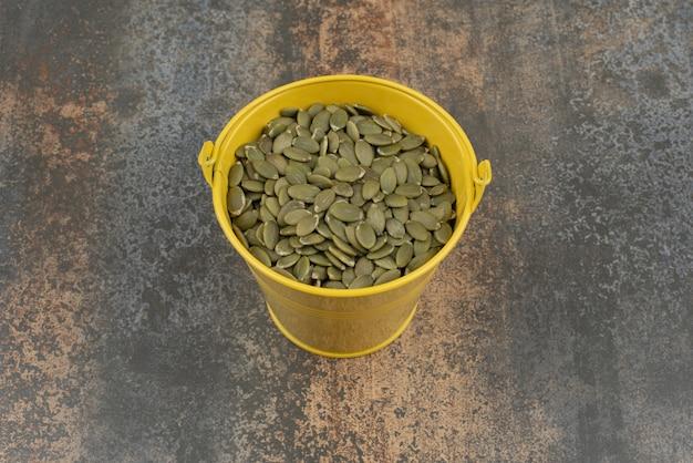 Желтое ведро, полное очищенных семян тыквы на мраморной поверхности