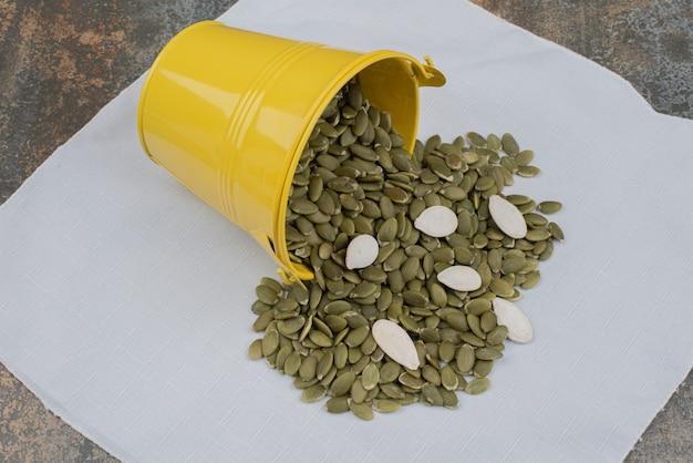 흰색 식탁보에 호박 껍질을 벗 겨 씨앗의 전체 노란색 양동이.