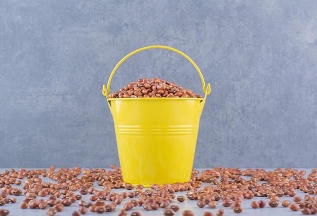 大理石の表面に散らばった山の中に小豆がいっぱい入った黄色いバケツ