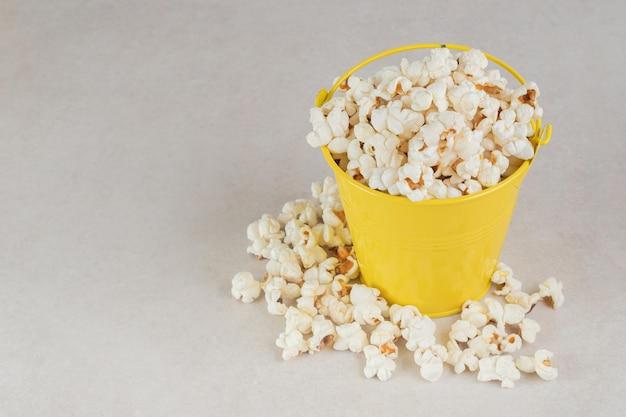 Secchio giallo troppo pieno di popcorn croccante sul tavolo di marmo.