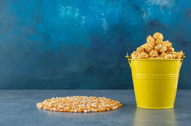 Yellow bucket of popcorn candy next to a neat pile of corn grain on blue