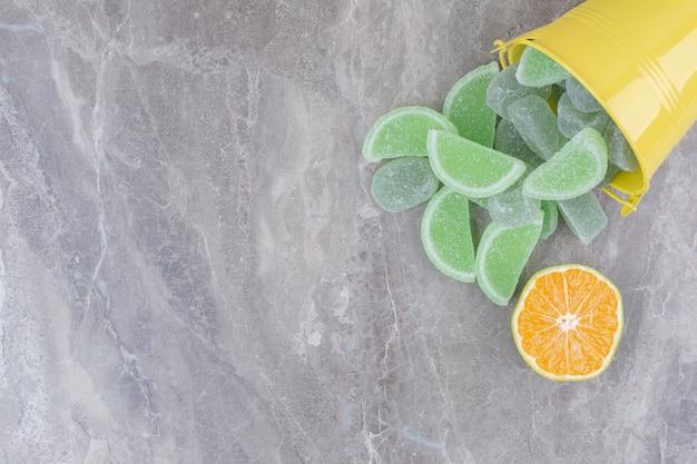 Желтое ведро с сахарным мармеладом и долькой апельсина на мраморном фоне.