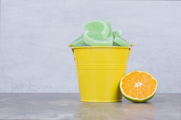 大理石の背景に砂糖マーマレードとオレンジのスライスと黄色のバケツ。