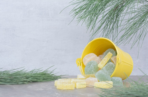 Yellow bucket with sugar marmalade on marble background.