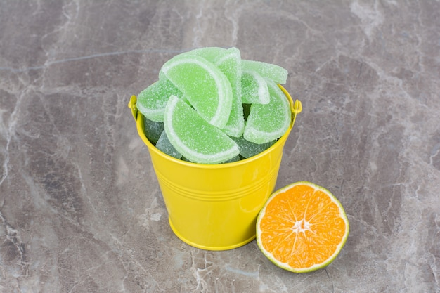 Yellow bucket with sugar marmalade and slice of orange on marble background.