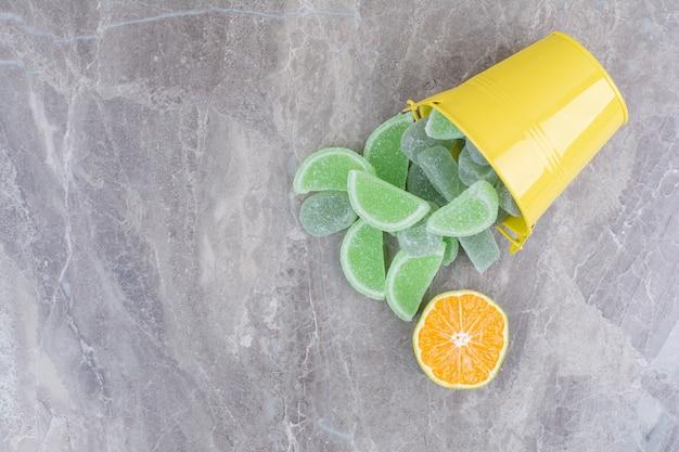 Secchio giallo con marmellata di zucchero e fetta d'arancia su sfondo marmo.