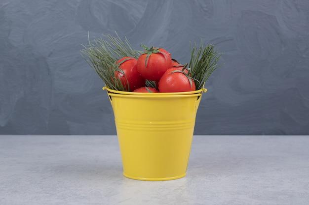 暗い背景にトマトと黄色のバケツ