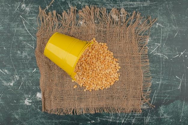 Желтое ведро с пшеницей на мешковине на мраморной поверхности