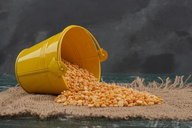 大理石の表面の黄麻布に小麦と黄色のバケツ