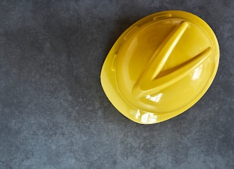 Yellow building helmet on wooden board