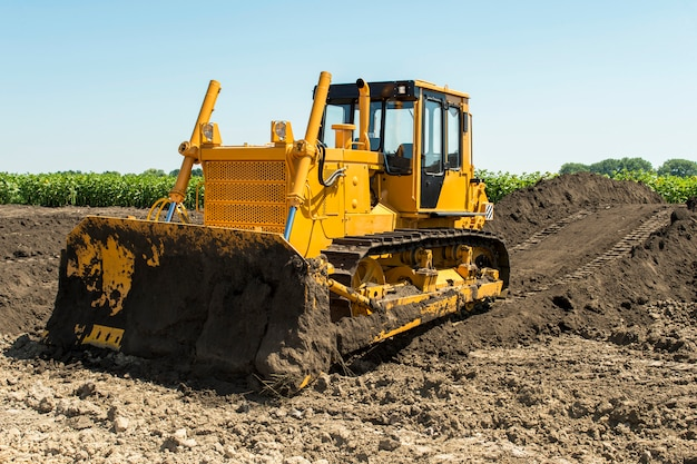 Желтый бульдозер с гусеничным трактором стоит в поле