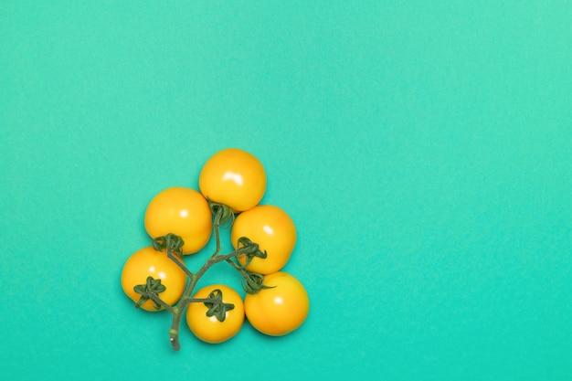緑の背景にトマトの黄色い束