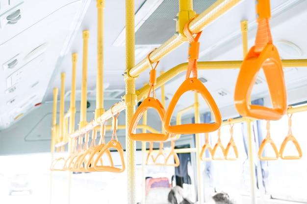 서있는 승객을위한 천장에 노란색 버스 핸들, 태국의 대중 교통 열차 난간 내부