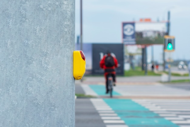 Желтая кнопка на светофоре для пешеходов на фоне пешеходного перехода и велосипедиста на велосипедной дорожке.