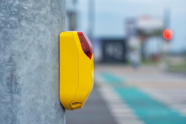 Желтая кнопка на светофоре для пешеходов на фоне пешеходного перехода и велосипедных дорожек для велосипедистов.