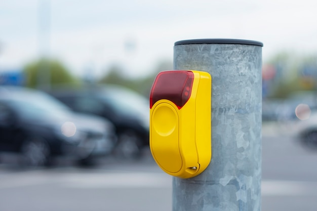 Желтая кнопка на светофоре для пешеходов на фоне дороги с автомобилями.